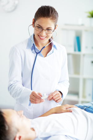 Female doctor listenning to male patient photo