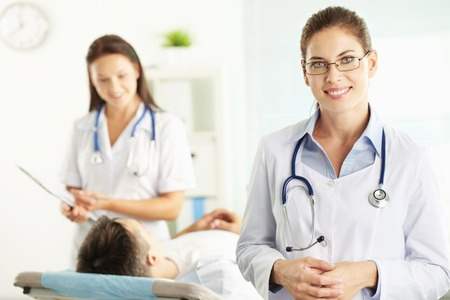 Confident female doctor with patient and nurse in the background photo