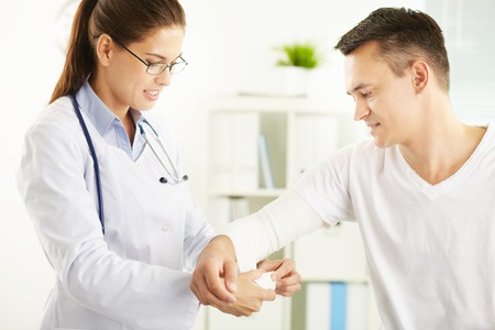 Woman doctor bandaging hand of male patient photo