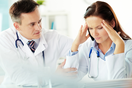 stress: Young doctor being nervous about her mistake, senior doctor trying to console her