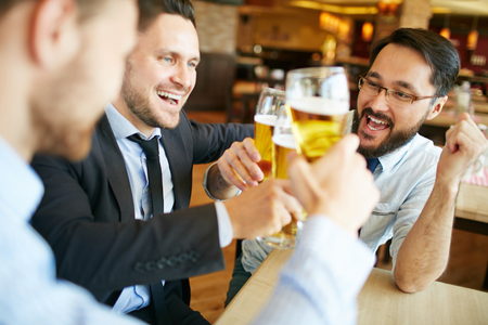 refreshment: Group of businessmen with beer cheering after meeting