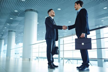 handshaking: Two partners with briefcases handshaking