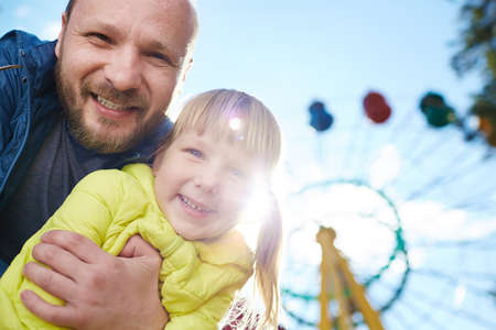adult entertainment: Man with daughter in amusement park Stock Photo