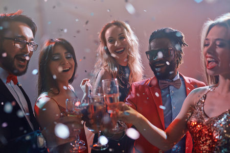 clubber: Group of ecstatic friends cheering with champagne at party