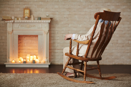 fireplace home: Woman in rocking-chair sitting in front of fireplace at home