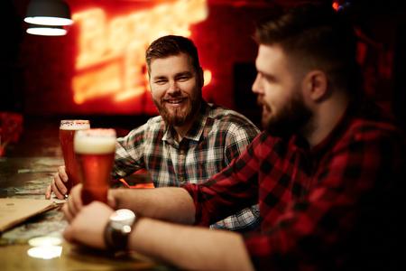 two friends talking: Two friends talking in bar by glass of beer