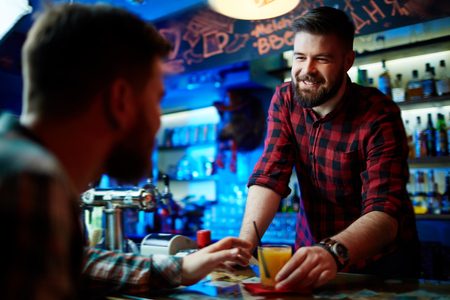barman: Friendly barman giving glass of juice to client