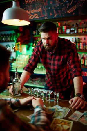 barman: Bearded barman looking at client by bar-counter