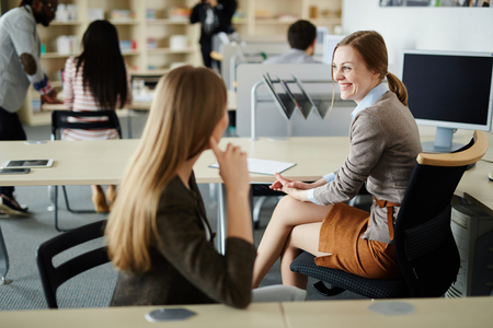 Working Environment: Two females talking in working environment in office