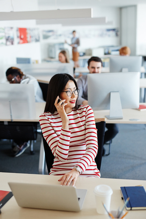 asian business man: Young secretary speakng on the phone at workplace