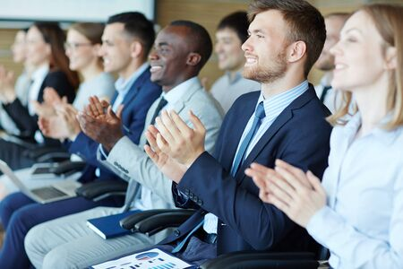 ovation: Young employees applauding to speaker at seminar Stock Photo