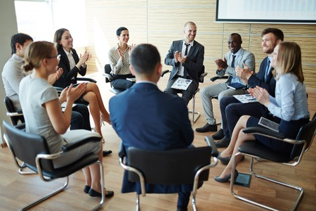 Group of colleagues applauding to one of employees in office Stock Photo