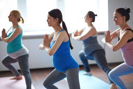 practicing: Active pregnant women practicing yoga Stock Photo