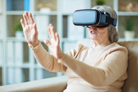 stimulator: Old woman gaining experienca with virtual reality stimulator