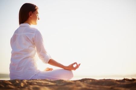 Escena tranquila de la hembra joven sentado en pose de loto en la playa por la mañana Foto de archivo