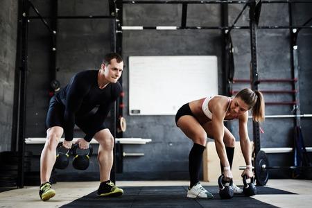 fitness hombres: Dos personas activas elevación WODS pesados ??en el gimnasio Foto de archivo