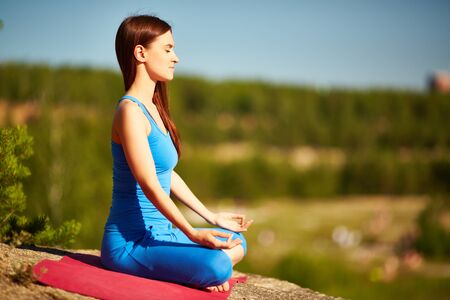 Young woman doing yog exercise outdoors