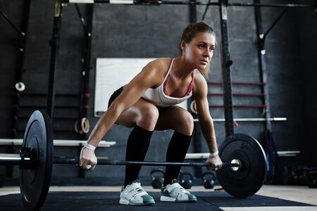 heavy weight: Young woman lifting heavy weight in gym