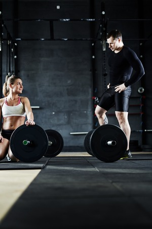 fitness hombres: Dos atletas jóvenes que interactúan en el gimnasio