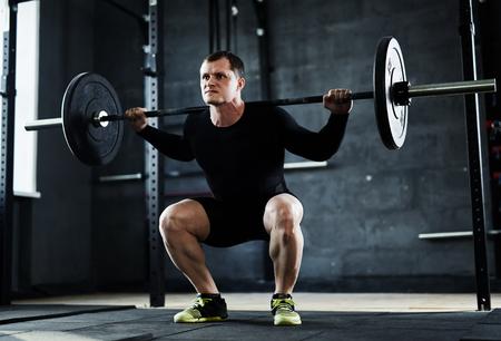 Starke junge Mann mit Krafttraining im Fitness-Studio Standard-Bild - 57365001