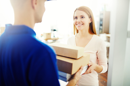 delivery: Happy young woman receiving a box from mailman Stock Photo