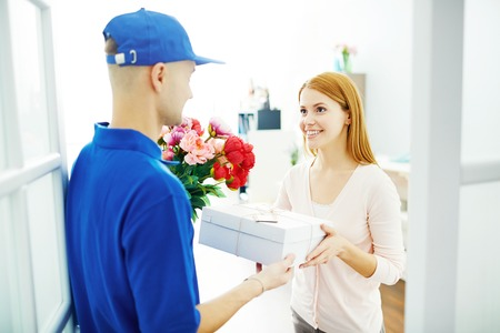 Delivery man giving flowers and present to pretty woman at home Stock Photo
