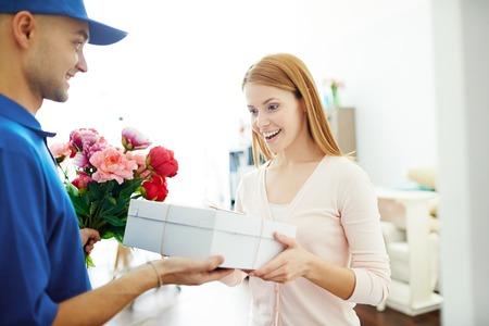Levering jongen die geschenkdoos en bloemen aan een verraste vrouw Stockfoto