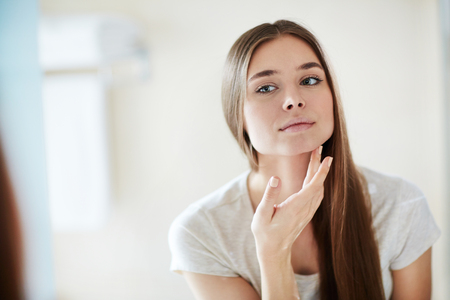 Young woman looking at mirror at home and applying cream on her face Stockfoto