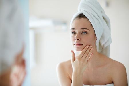 mimos: Mujer joven que mira en el espejo en el baño y mimando a su cara Foto de archivo