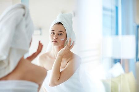 Jonge vrouw die stichting of vochtinbrengende crème op haar gezicht voor spiegel toepast