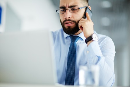 displeased businessman: Businessman looking at his laptop and calling to IT helpdesk