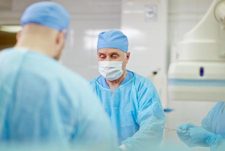 Älterer Chirurg die Operation durchführen mit seinen Assistenten