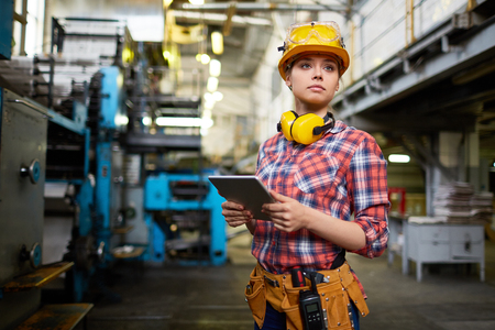 Pretty female student doing practical work at factory Stock Photo