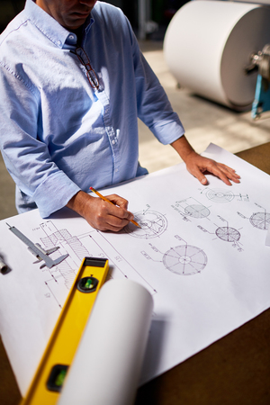 industry architecture: Mature engineer drawing technical details