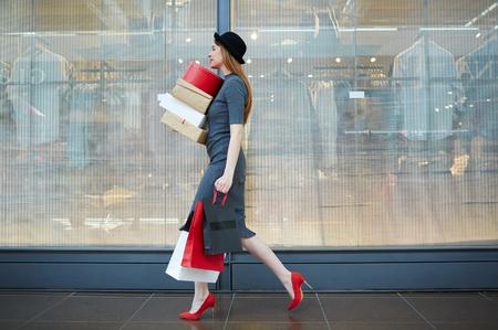 エレガントな女性の袋や箱でモールを歩いて