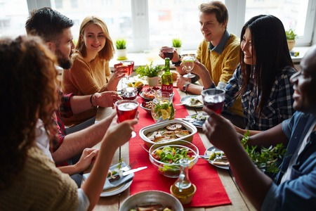 lunch table: Friends sitting at dining table and toasting with wine Stock Photo
