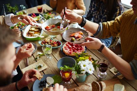 Las personas que se sientan en la mesa de comedor y alimentación
