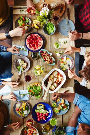 Vista de ángulo alto de la mesa de fiesta y la gente de comer