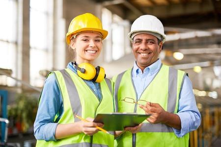 Ingénieur expérimenté avec son jeune stagiaire féminine Banque d'images - 57362747