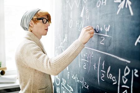 hombre escribiendo: Fórmula de la escritura joven especialista en la pizarra