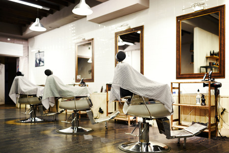 Empty barbershop with arm-chairs, barber equipment and mirrors on walls Stock Photo