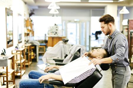barbershop: Bearded man in arm-chair sitting in barbershop