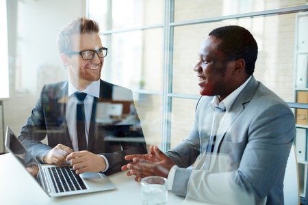 african man: Employees discussing data at workplace Stock Photo