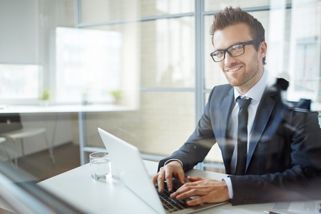 business men: Young employee typing in office