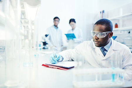 clinician: Clinician writing down scientific analysis Stock Photo