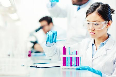 characteristics: Young woman analyzing chemical characteristics of liquids Stock Photo