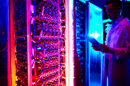 storage: Young engineer working in data storage center Stock Photo