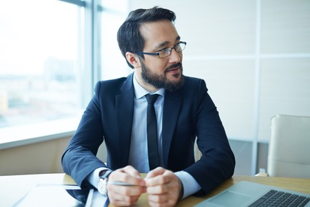 looking aside: Confident businessman looking aside at workplace