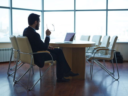 tired businessman: Tired businessman sitting by table in office