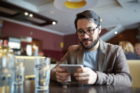 work addicted: Businessman with cellphone sitting in cafe